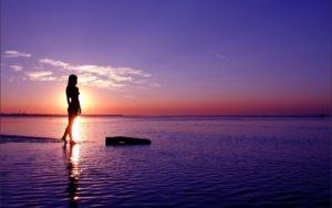 woman_standing_on_the_beach_at_sunset-wide